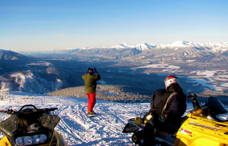 Snowmobilers looking at scenic valley